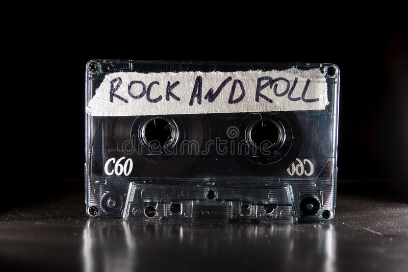 Vintage old film music cassette isolated on black background with the inscription rock and roll, background music, music. Lovers royalty free stock photo