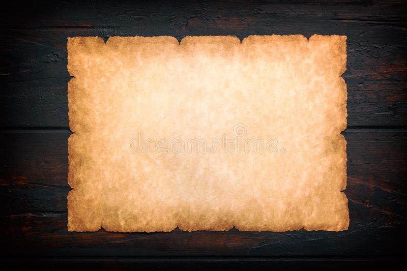 Vintage old grunge background texture paper scroll on dark wooden background. Brown burnt paper background. Frame mockup stock image