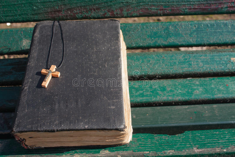 Vintage old holy bible book, grunge textured cover with wooden christian cross. Retro styled image on wood background. stock photos