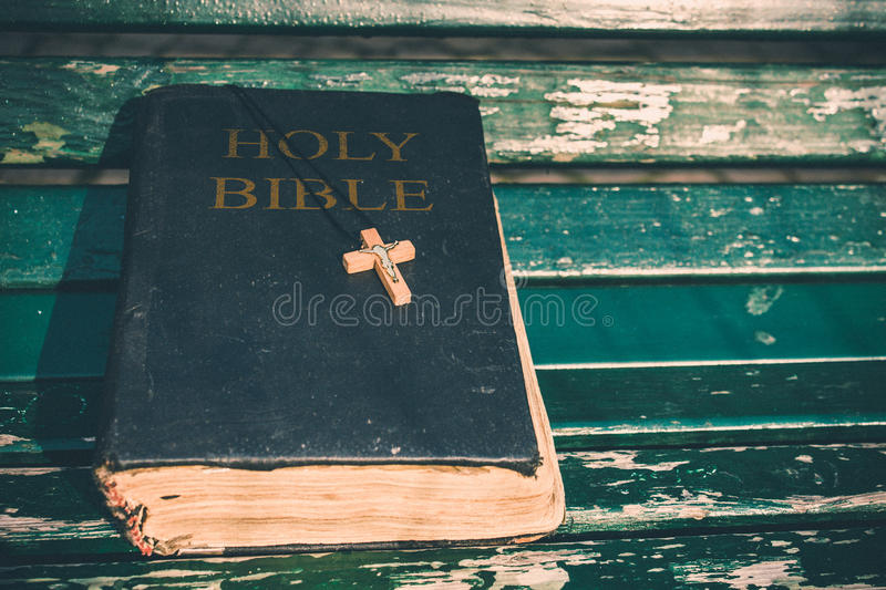 Vintage old holy bible book, grunge textured cover with wooden christian cross. Retro styled image on wood background. stock image