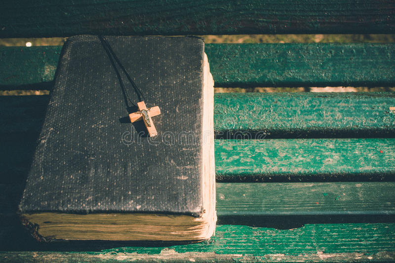 Vintage old holy bible book, grunge textured cover with wooden christian cross. Retro styled image on wood background. royalty free stock photos