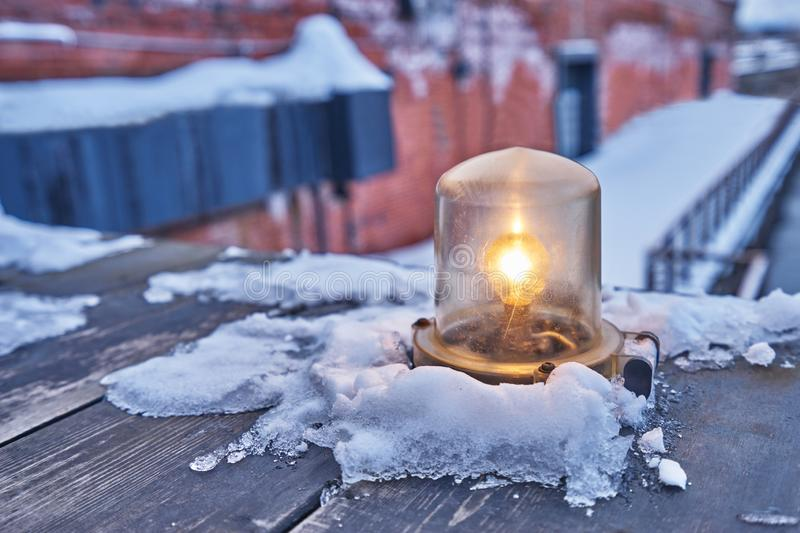Vintage old orange light lamp with snow cover in ground at Kanemori red brick in Hakodateใ. Vintage old orange light lamp with snow cover in ground at stock images
