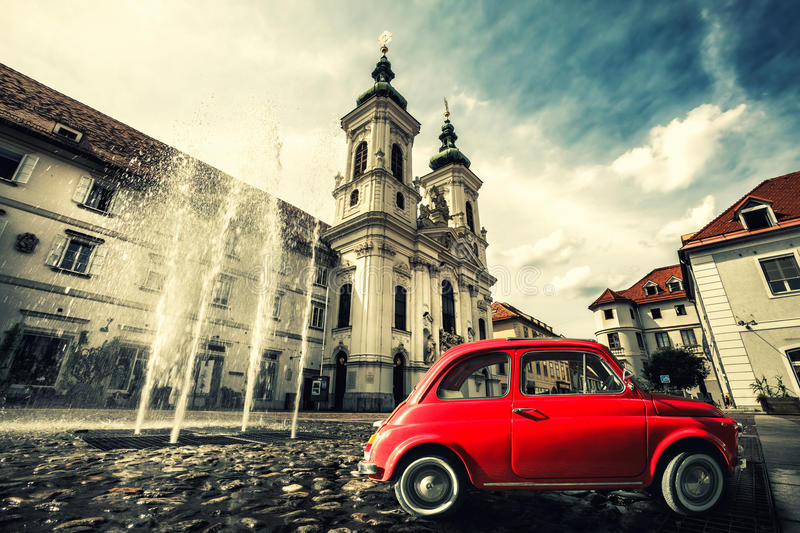 Vintage old red car scene. Graz, Austria. A small red vintage car parked in the old town square of Graz in Austria. splash of a fountain and Mariahilferkirche stock photo