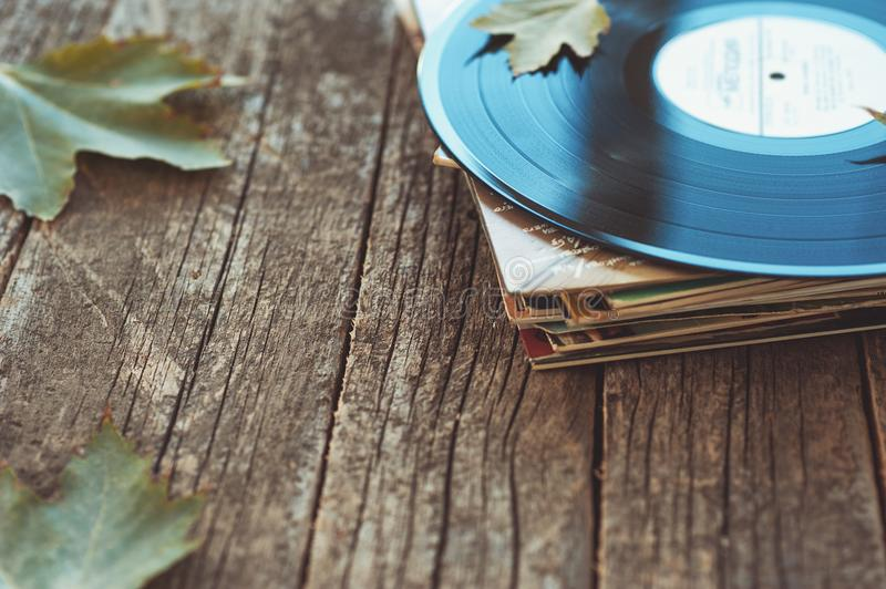 Vintage old vinyl records on wooden autumn background, selective focus decorated with few leaves. Music, fashion, texture, stock photos
