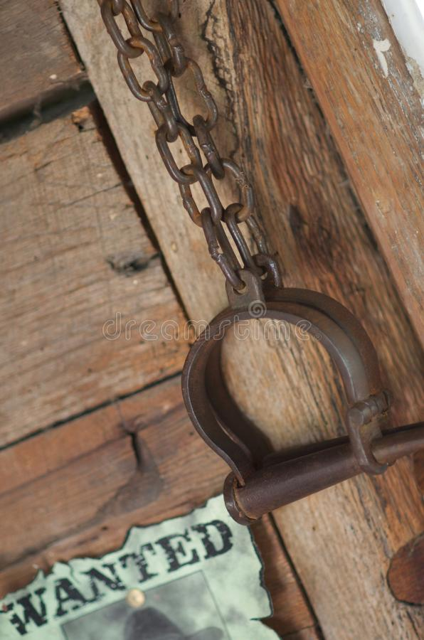 Vintage old western prison shackles and reward fug. American West Legend United States old wanted reward fugitive poster with ancient western prison shackles on royalty free stock photography