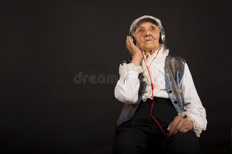 Vintage old woman in glitter with headphone stock photos