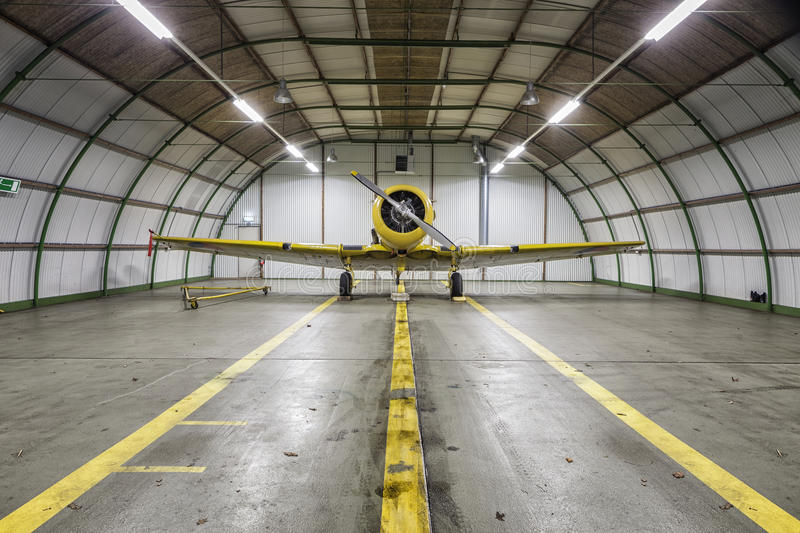 Vintage old yellow war plane inside of a empty hangar. Vintage old yellow war plane inside of a clean empty hangar royalty free stock photography
