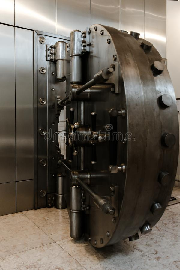 Vintage open steel bank vault door. With its security system and manual closing stock image