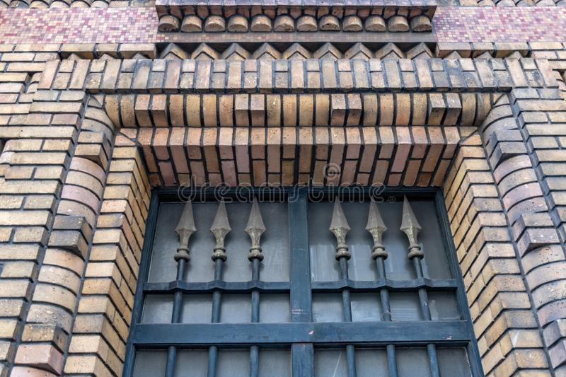 Vintage ornate gratings of doorway in old brick wall of building in Paris France. Architectural details closeup. Antique lattice stock photography