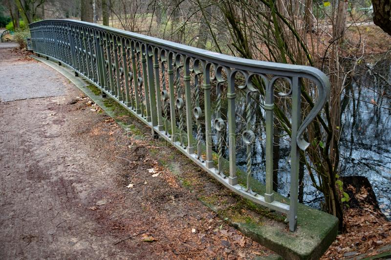 Vintage ornate metal railing fence of old bridge near pond in Tiergarten park of Berlin Germany. Tranquil landscape with nobody. Tranquil landscape with nobody royalty free stock photography