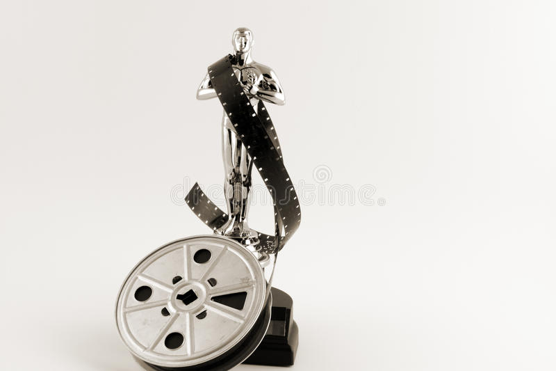 Vintage Oscar statue with movie reel desaturated royalty free stock photos
