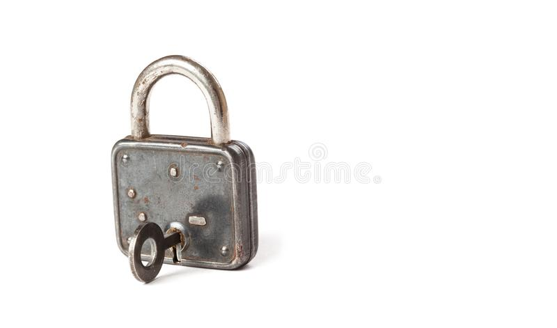 Vintage padlock with key in hole. hanging lock close-up. texture and detailed. white background. royalty free stock photos