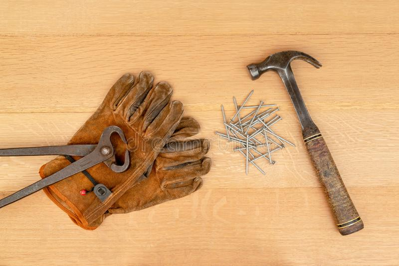 Vintage Pair Of Cutting Nippers Pliers Work Gloves Hammer Nails Wood Background royalty free stock images