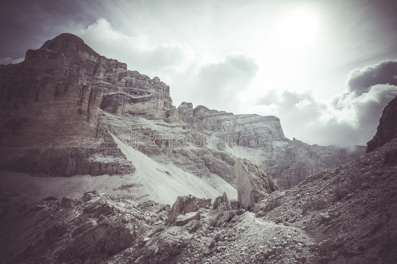 Vintage panorama of giant boulders expanse with Giussani Mountain Hut at the foot of Tofana summit. Dolomites, Cortina d`Ampezzo, Italy royalty free stock photos