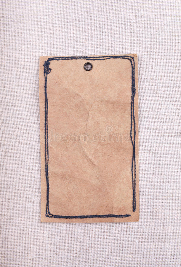 A vintage paper tag. On fabric background stock photography