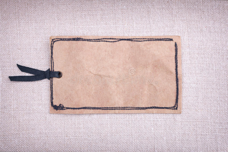 A vintage paper tag. On fabric background royalty free stock photo
