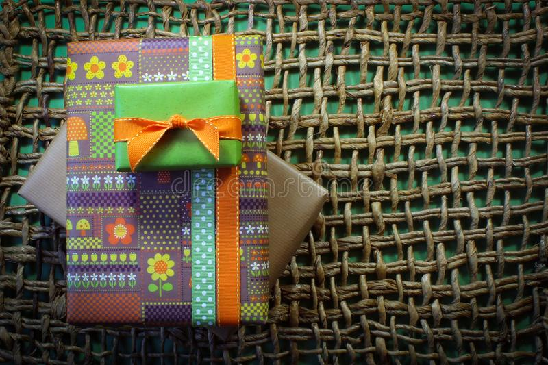 Vintage paper wrapped gifts on woven mat with green background. Aligned left, horizontal aspect stock image
