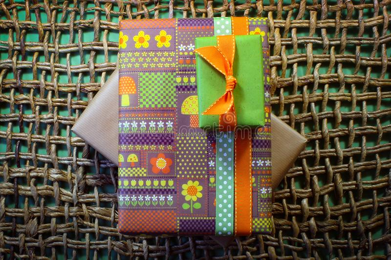 Vintage paper wrapped gifts on woven mat with green background. Centered, horizontal aspect stock photography