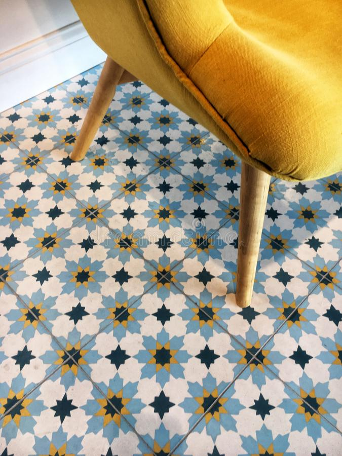 Vintage pattern. Ceramic tiles with vintage pattern and yellow sofa royalty free stock images