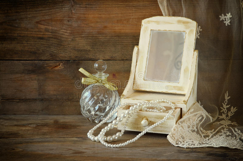 Vintage pearls , antique wooden jewelry box with mirror and perfume bottle on wooden table. filtered image.  royalty free stock photo