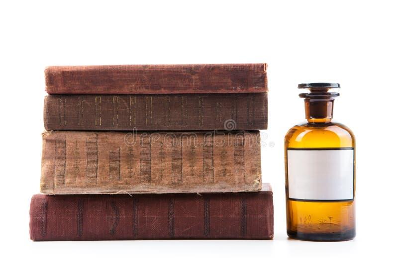 Vintage pharmacy bottle on white background with books. Vintage medicine pharmacy bottle with books on white background royalty free stock photography