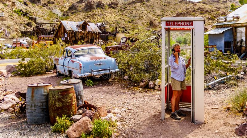 Vintage phone booth and vintage cars in the old mining town of El Dorado in Nevada, USA. Vintage phone booth and vintage cars used in movies on display in the royalty free stock photo