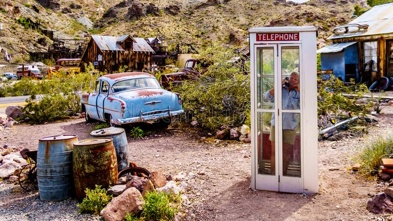 Vintage phone booth and vintage cars in the old mining town of El Dorado in Nevada, USA. Vintage phone booth and vintage cars used in movies on display in the stock image