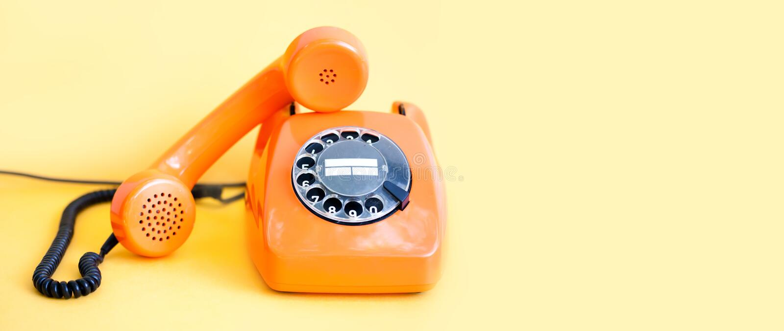Vintage phone busy handset receiver on yellow background. Retro style orange telephone communication call center concept. Shallow depth field. copy space