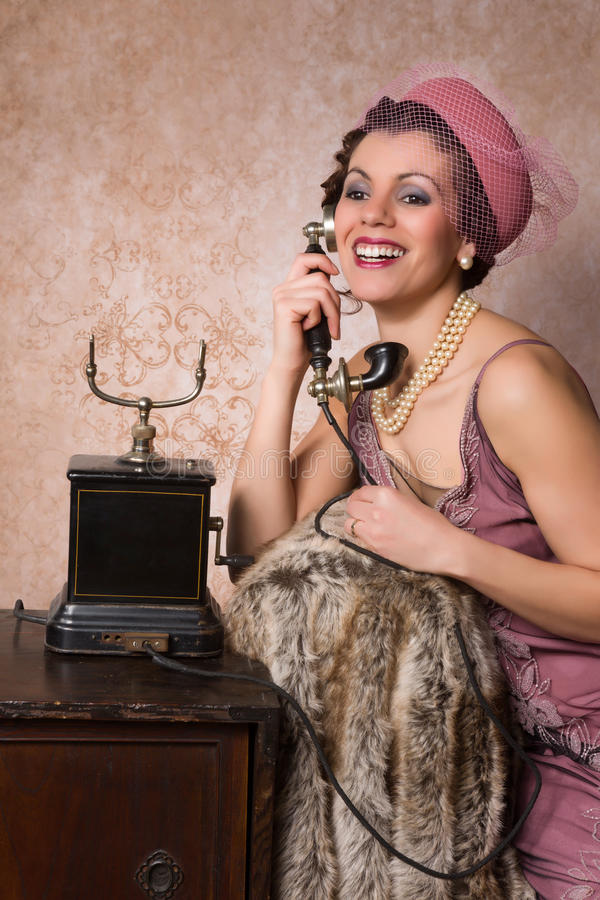 Vintage phone call. Stunning vintage 1920s woman talking on an antique telephone stock photos