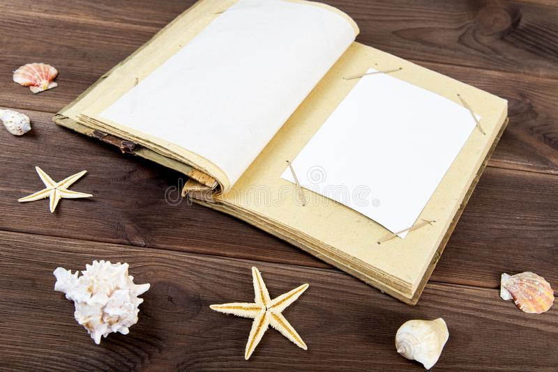 Vintage photo album on wooden background with seashells. Memories of the rest of the sea royalty free stock images