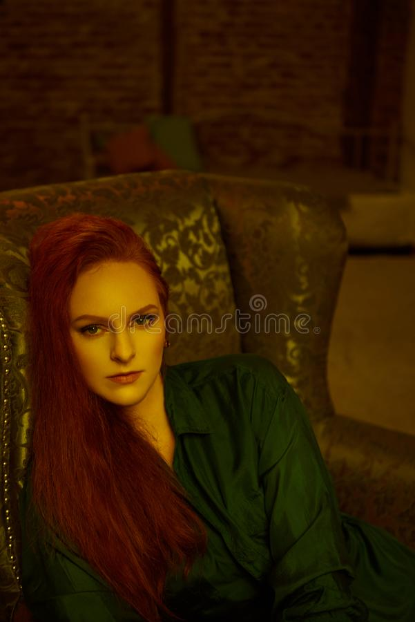 Vintage photo of Beautiful red haired young woman posing in old loft apartment in Tbilisi. Close up portrait Ginger lady posing in loft apartment in Tbilisi. She royalty free stock images