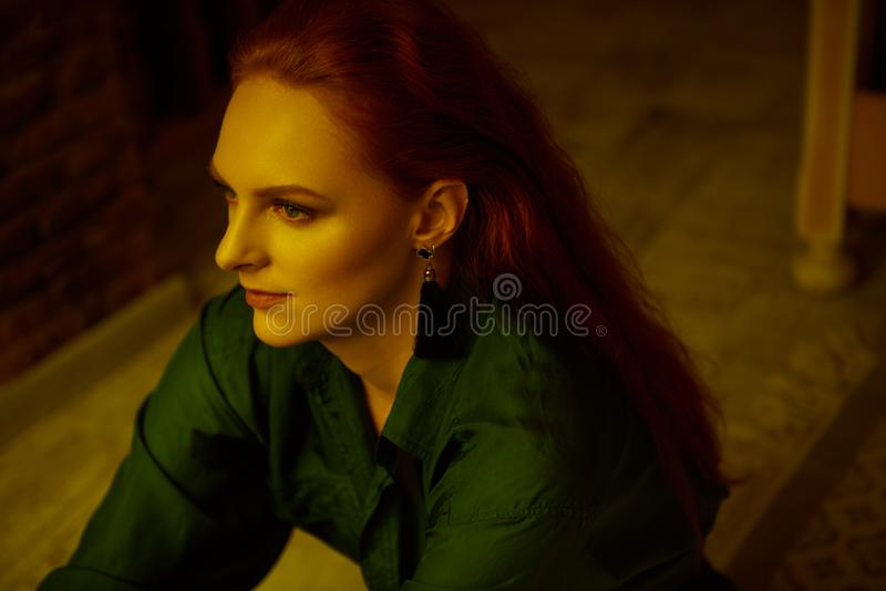 Vintage photo of Beautiful red haired young woman posing in old loft apartment in Tbilisi. Close up portrait Ginger lady posing in loft apartment in Tbilisi. She royalty free stock photos