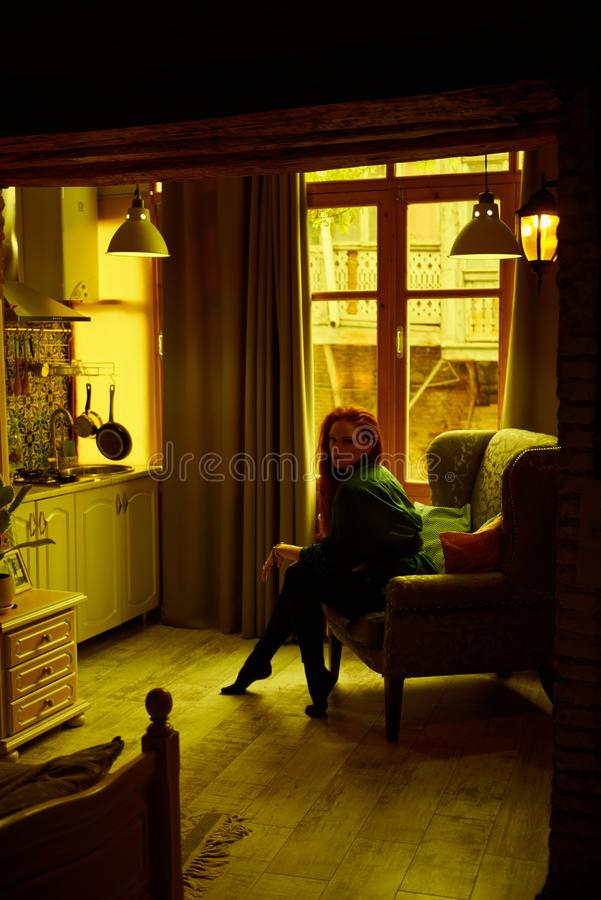 Vintage photo of Beautiful red haired young woman posing in old loft apartment in Tbilisi. Ginger lady posing in arm chair in loft apartment in Tbilisi. She stock photo