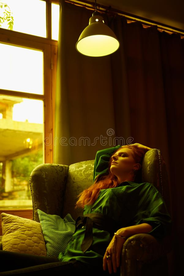 Vintage photo of Beautiful red haired young woman posing in old loft apartment in Tbilisi. Ginger lady posing in arm chair in loft apartment in Tbilisi. She stock image