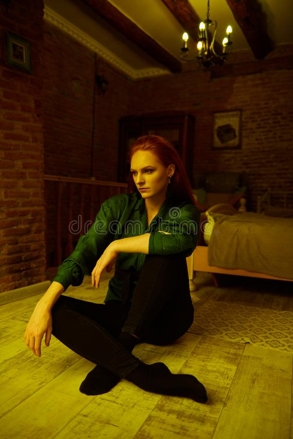 Vintage photo of Beautiful red haired young woman posing in old loft apartment in Tbilisi. Ginger lady posing in loft apartment in Tbilisi. She wears green shirt stock photo