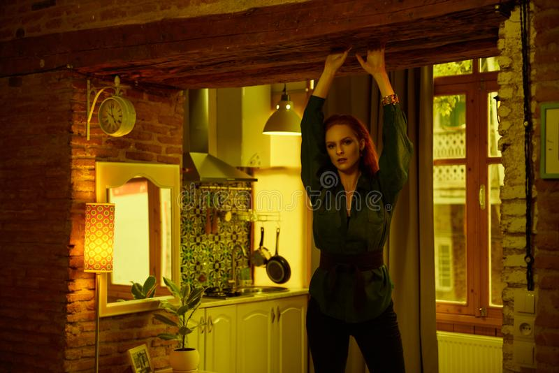 Vintage photo of Beautiful red haired young woman posing in old loft apartment in Tbilisi. Ginger lady posing in loft apartment in Tbilisii. She wears green stock photo
