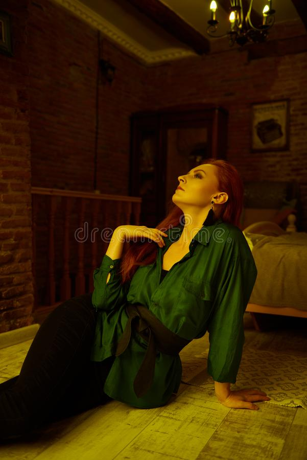 Vintage photo of Beautiful red haired young woman posing in old loft apartment in Tbilisi. Ginger lady posing in loft apartment in Tbilisi. She wears green shirt royalty free stock photo