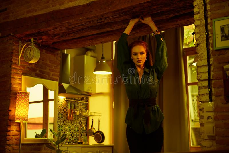 Vintage photo of Beautiful red haired young woman posing in old loft apartment in Tbilisi. Ginger lady posing in loft apartment in Tbilisii. She wears green stock photography