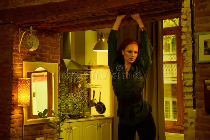 Vintage photo of Beautiful red haired young woman posing in old loft apartment in Tbilisi. Ginger lady posing in loft apartment in Tbilisii. She wears green royalty free stock photography