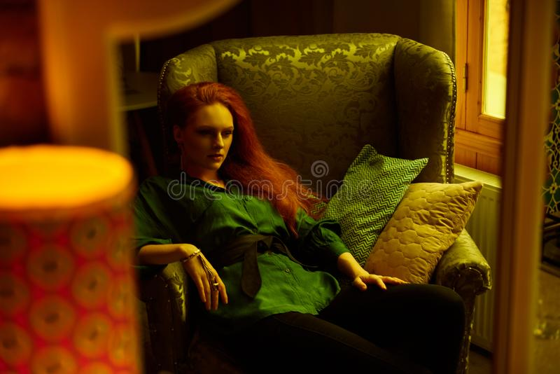 Vintage photo of Beautiful red haired young woman posing in old loft apartment in Tbilisi. Mirror reflection of Ginger lady posing in loft apartment in Tbilis royalty free stock image