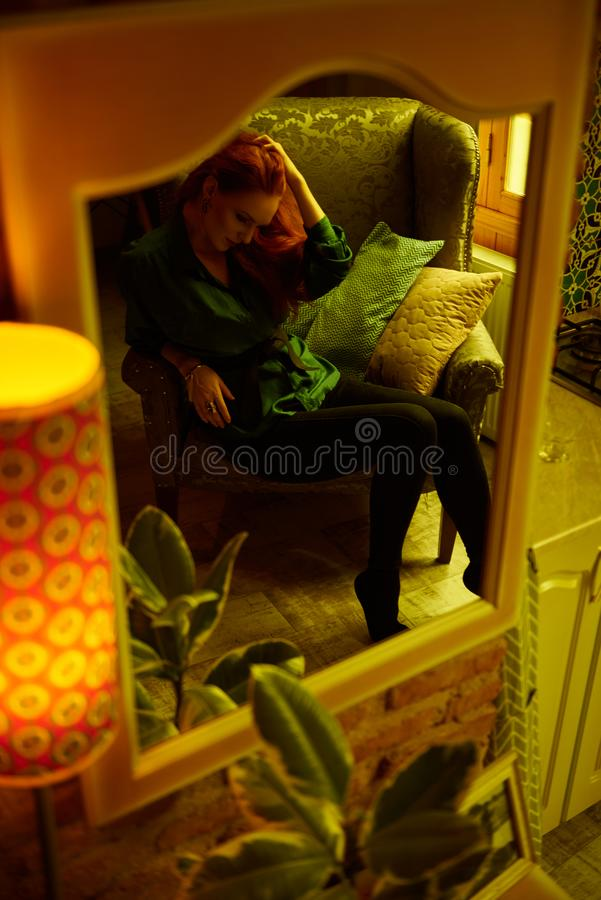 Vintage photo of Beautiful red haired young woman posing in old loft apartment in Tbilisi. Mirror reflection of Ginger lady posing in loft apartment in Tbilis stock images