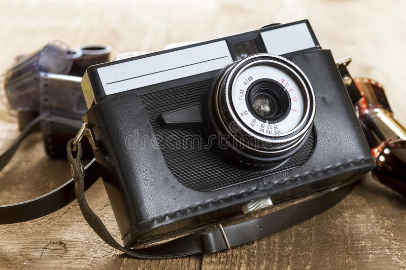 Vintage photo camera and blank film strip. Old camera and blank film strip on wooden table stock photos