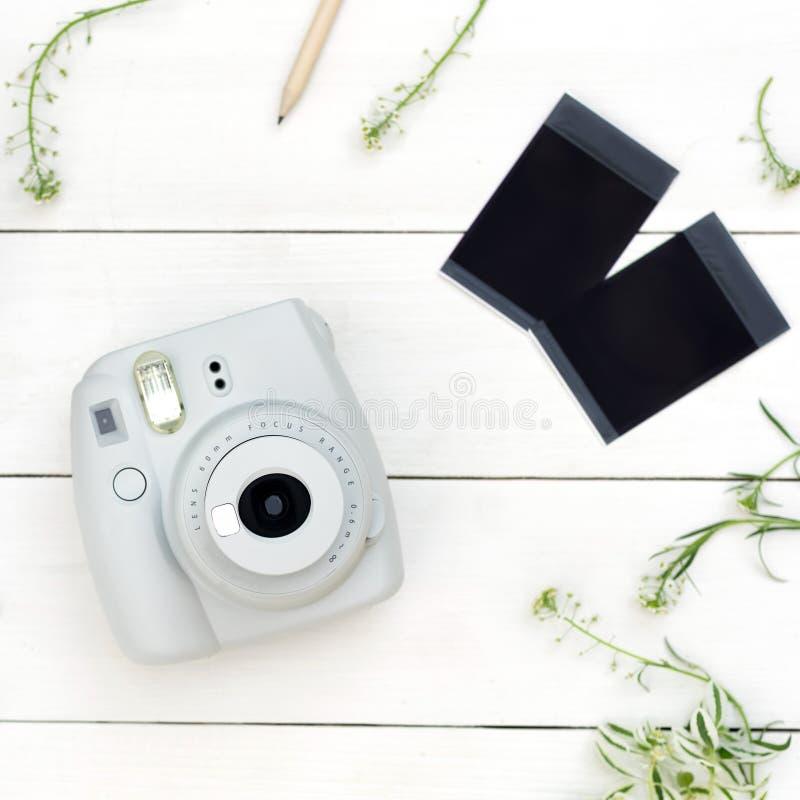 Vintage photo camera on white background with photo cards. Polaroid camera. Instax white camera. Flat lay. Eye bird view stock photo
