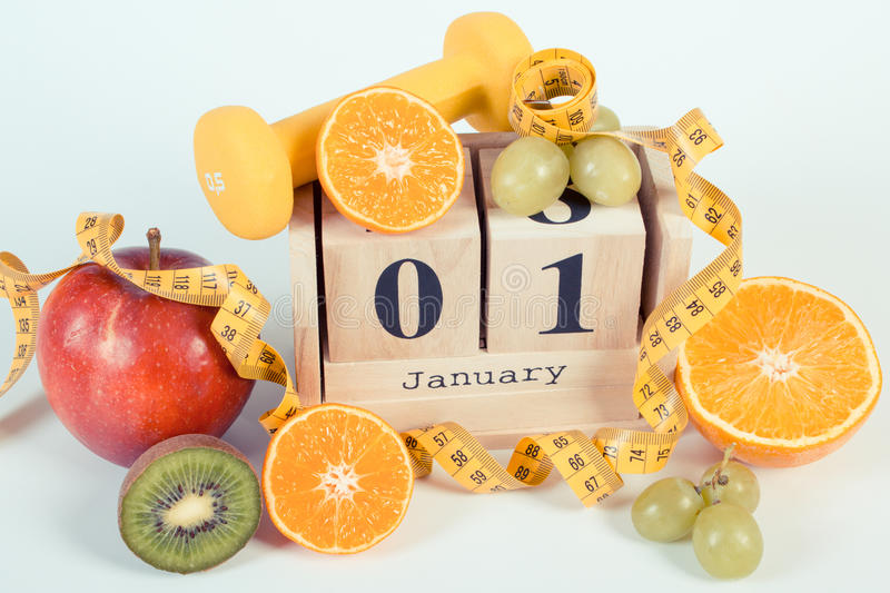 Vintage photo, Cube calendar, fruits, dumbbells and tape measure, new years resolutions. Vintage photo, January 1 on cube calendar, fresh fruits, dumbbells and stock photo