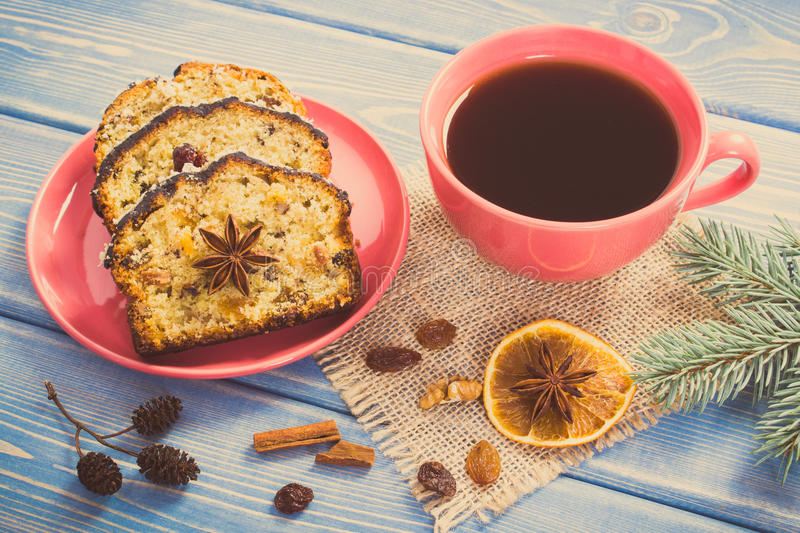 Vintage photo, Cup of coffee, fresh baked fruitcake for Christmas and spruce branches. Vintage photo, Cup of black coffee, pieces of fresh baked homemade stock photo