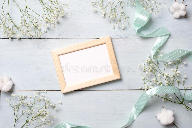 Vintage photo frame with flowers on light blue wooden background. Banner mockup for congratulation with womans or mother day, wedd. Ing invintation, easter card stock photo