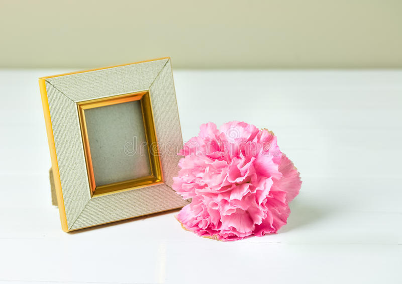 Vintage photo frame and pink carnation flower on wooden table. Vintage photo frame and pink carnation flower on wooden table, Still life style stock photography