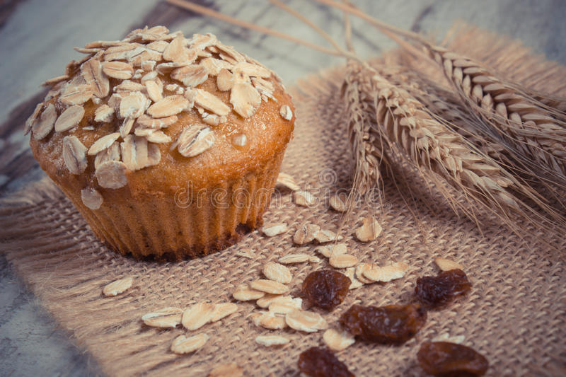 Vintage photo, Fresh muffin with oatmeal baked with wholemeal flour and ears of rye grain, delicious healthy dessert stock photo