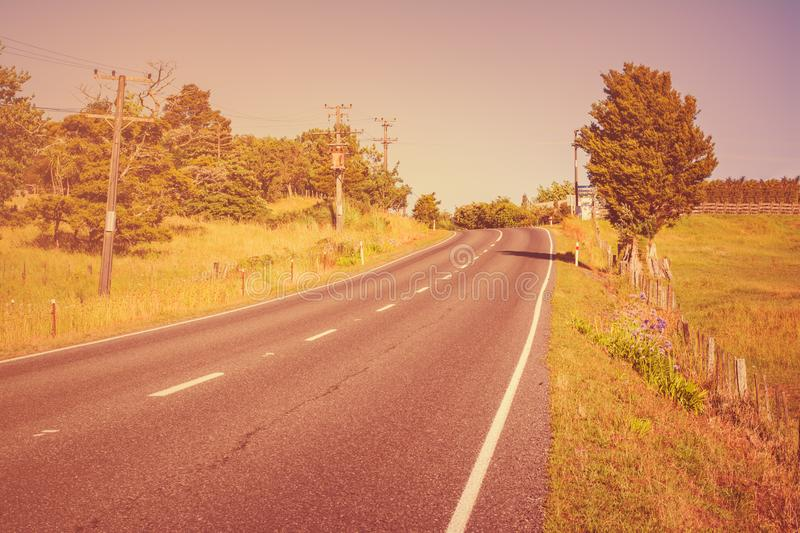 Vintage photo of a highway road going up hill with green grass field under blue sky. royalty free stock photography