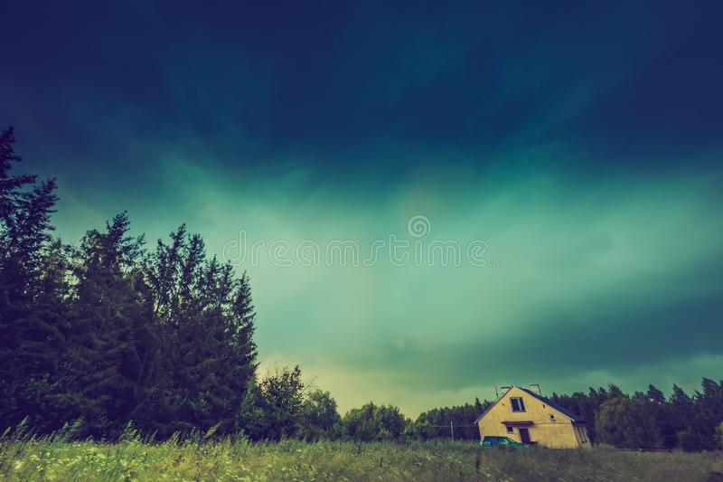 Vintage photo of storm sky over meadow, house and forest. Summer dark landscape stock photo
